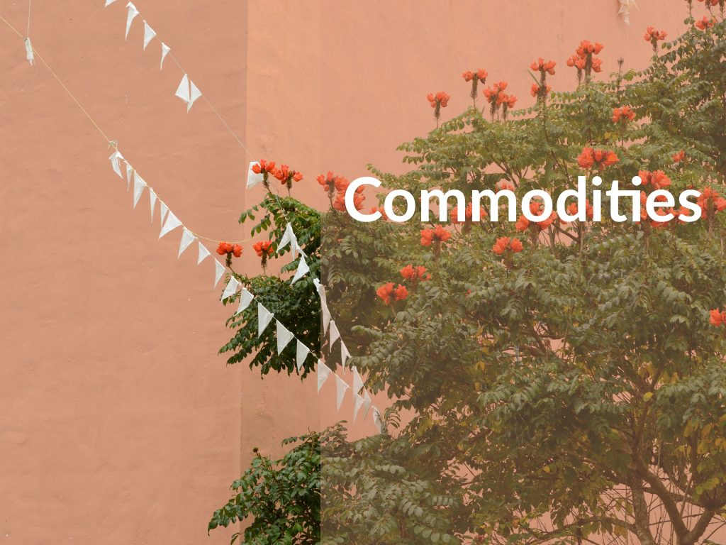"Green tree with red flowers and white flags attached. Caption over photo saying ""Commodities."" Investing in commodities."