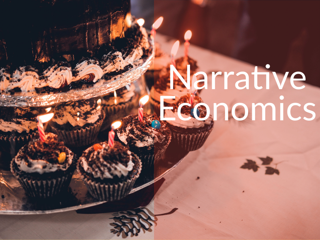"""Chocolate cupcakes topped icing and M&Ms with candles on top surrounding a cake. Caption saying """"Narrative Economics."""""""